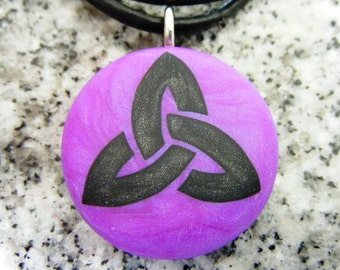 Trinity Symbol hand carved on a Polymer clay purple pearl color background. Pendant comes with a FREE Necklace