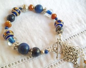 Boho Style Beaded Bracelet Cobalt Blue and Caramel Lampwork Beaded Bracelet Blue Lapis Blue Howlite and Silver Cross Charm