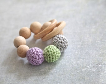 Teething toy with crochet wooden beads and 2 wooden rings. Light grey, light lila, green wooden beads rattle.
