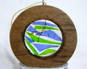 Salvaged, teak paneling round, filled with shards of blue and green stained glass.