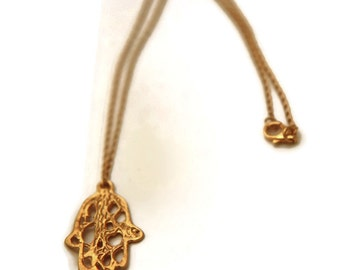 Gold  HAMSA hand  pendant  from the sabrawear collection  .