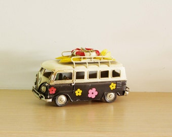 Retro VW van, hippie van in black and creamy white with painted flowers and surfboards on the baggage rack, VW collectible miniature