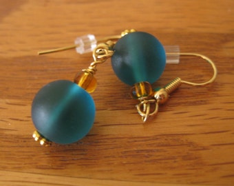 Deep teal sea glass beads with amber accents on gold wire earrings