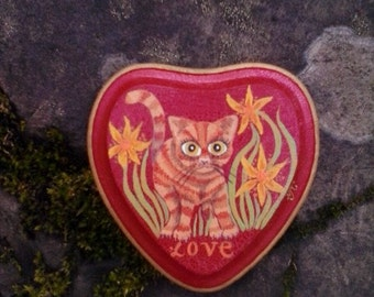 Orange tabby cat on red wooden heart