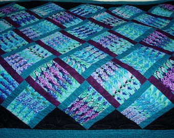 Handquilted bed quilt in stacked design with blues and purples