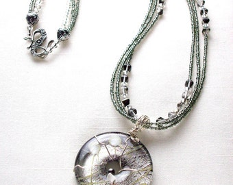 Silvery donut pendant necklace with carnelian glass bead, white mother of pearl chip and hematite accents on 3 strands