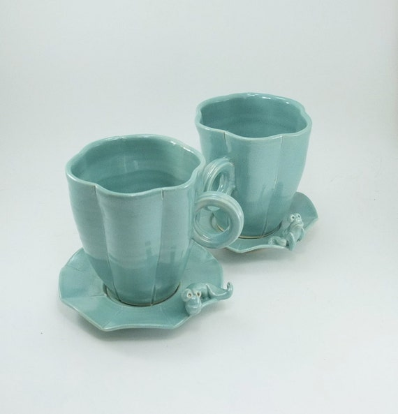 pair of cups and saucers with frog and caterpillar
