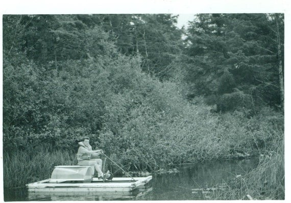boy on a pedal boat at the lake summer vacation vintage