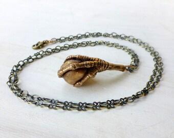 Bird claw grasping a bead pendant