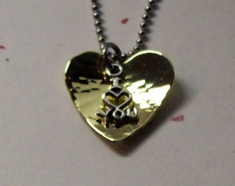 """I love you pendant necklace of a hammered and cupped brass heart with a sterling silver """"I (heart) you"""" charm on a stainless steel chain."""