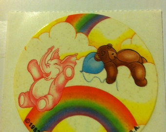 Elephant sliding down rainbow,and bear sleeping on clouds vintage sticker, 1983