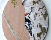 A real painters palette with an oilpainting of a woodpecker on it.