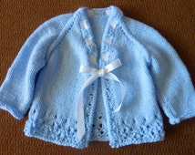 Girl's Ribbon Tie Hand Knit Tie Sweater made of a soft baby blue acrylic yarn and adorned with a white satin ribbon