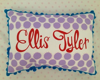 Pillow in soft lavender polka dots, bright red and turquoise. Personalized with name.