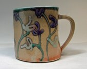 shino cup with purple and green flowers and a jade green interior - BlackForestPottery