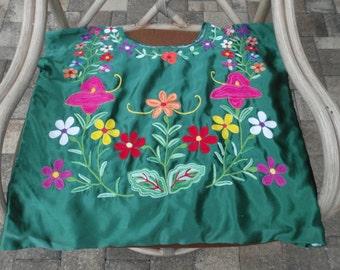 Magnificent Mexican Huipil, a colorful flower arrangement against a green silk  background