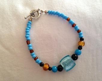 Blue beaded bracelet with toggle closure.