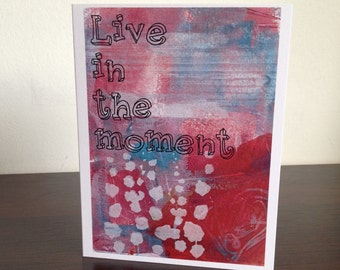 "Card. Quote. ""Live in the moment."" Flower design. Red. Blue. Purple."