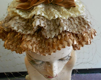 1950's burnt orange velvet covered wire hat, with three rows of wave shaped straw in amber, tan and brown