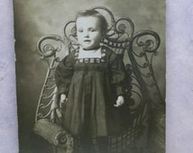 Adorable Little Boy in Black Dress - Standing in Wicker Chair - Vintage Real Photo Postcard