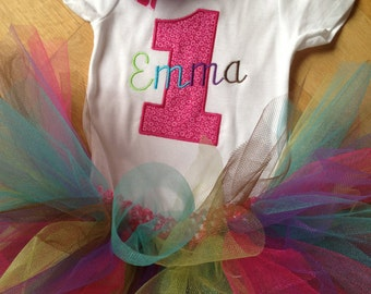 1st birthday bodysuit with name, colorful tutu, and matching hair bow