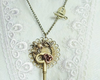 Art Nouveau key necklace adorned with roses and partridge.