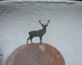 Fused glass square tile in a unusual shape with a black silhouette of a stag on a watercolor style sphere.