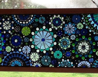 Stunning glass mosaic window in shades of green and blue circular pattern