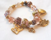 Pink and Gold Charm Bracelet with hearts, Fleur de Lis, and Crown charms