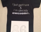 DISCOUNTED -- Good but Not Perfect -- #86, see photos -- I just got here & I'm already awesome.  -- black snapsuit, size 0-3 months