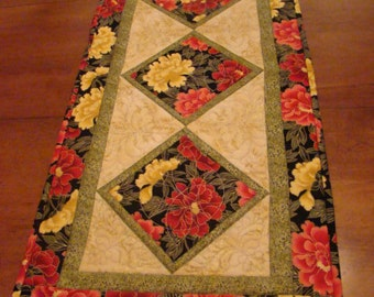 Lotus flower tablerunner with gold etchings.  This table runner measures16 x 34 inches and has extensive machine quilting.
