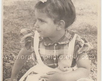 Vintage/Antique side view photo of a beautiful little girl holding her doll