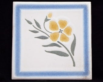 Blue and white tile with yellow flower