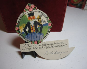 1920's art deco die cut P.f. volland novelty bridge tally place card with riddle and hidden answer rosy cheeked dutchman and  windmill