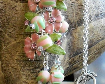 Pale pink/peace polymer rosettes and metal flowers with crystal centers on a silver necklace with toggle clasp.