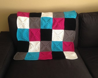 Bright, colorful and soft crochet baby blanket in hot pink, gray, white, blue and black