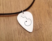 "Guitar shaped carving on a solid aluminium pick plectrum pendant. Hand cut and mounted on a black leather 18"" necklace"
