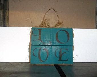 This sign is made with 4 blocks glued together and on the outside of the blocks edges wrapped with burlap and a rope handle