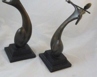 Set of Two metal sculptures playing instraments on pedistals
