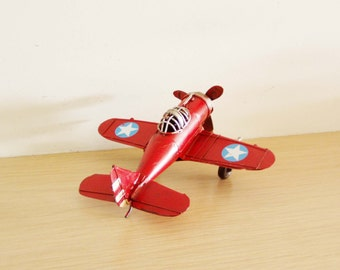 Red metal aeroplane, retro collectible toy plane with partly open cockpit and moving propeller, vintage airplane miniature, mid nineties