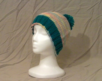 Handknit toque with a pom-pom.