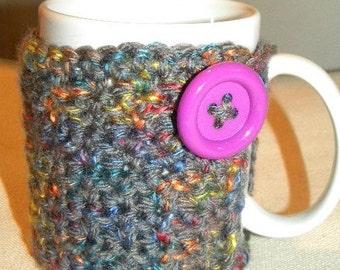 Crochet reusable coffee cozy with button.