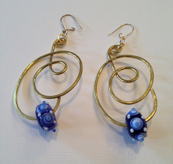 Brass earrings with flattened wire work and blue glass bead with white spiral effects and white dots