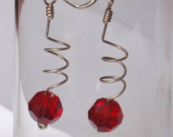 Bright  Ruby Red Crystals are suspended  on a simple sterling silver coil.  Earrings are mounted on sterling silver lever back earwires.
