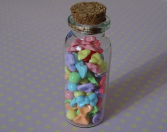 Decorative bottle/vial containing polymer clay bows and bon bons