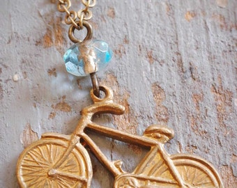 little vintage brass bicycle charm necklace. repurposed old bike charm & aqua blue czech glass bead on antiqued brass chain. ooak by val b.