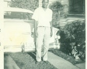 1958 African American Black Man Standing Behind Car in Driveway 1950s Summer Vintage Black White Photo Photograph