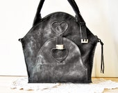 Black suede bag with handles and a large front pocket