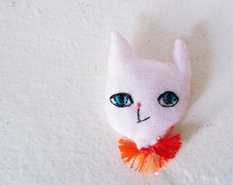 Little fabric cat magnet and its pompoms necklace.