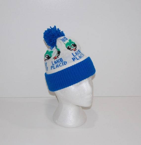 Lake Placid 1980 Winter Olympics Blue & White Knit Ski Beanie Hat with Blue Shaggy Pom and Green Head Raccoon Graphic